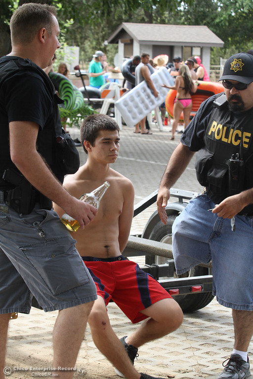 . A man is arrested in the Irvine Finch parking lot after dropping an open alcohol container on the ground  before he could participate in the  Labor Day weekend float the Sacramento River  on Sunday, September 1, 2013. (Frank Rebelo/Staff Photo)