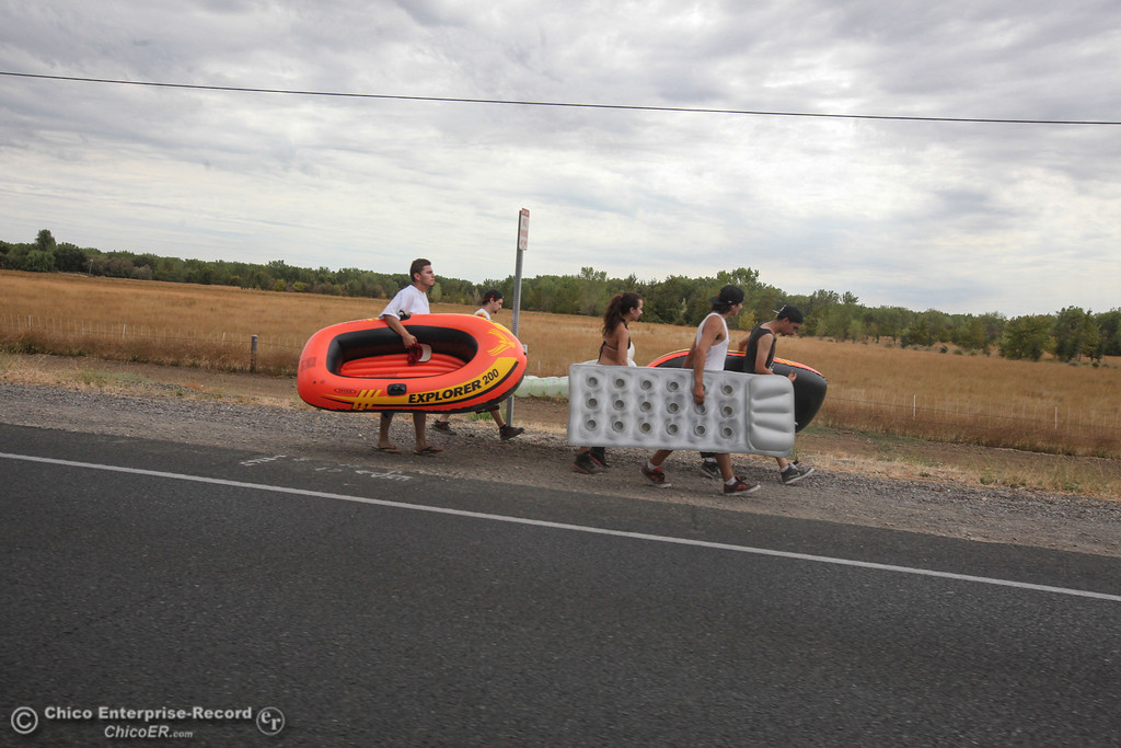 . Floaters walk down Highway 32 to the Irvine Finch boat launch on Labor Day weekend to float the Sacramento River  on Sunday, September 1, 2013. (Frank Rebelo/Staff Photo)