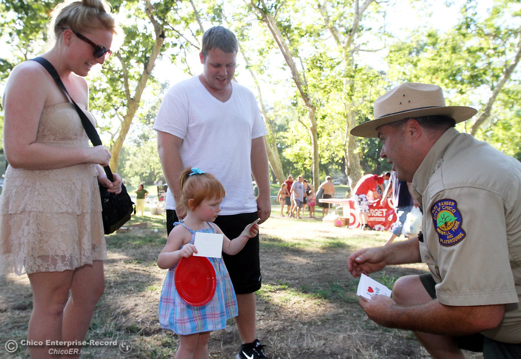 """. Bidwell Park Ranger Shane Romain hands out \""""Junior Ranger\"""" and \""""I love Bidwell Park\"""" stickers to Amiah Carroll, 2 yrs old, of Chico with her mom and dad, Taleah Melenhorst and Spencer Carroll during the 29th Annual National Night Out in August 2012. (Ty Barbour/Chico Enterprise-Record)"""