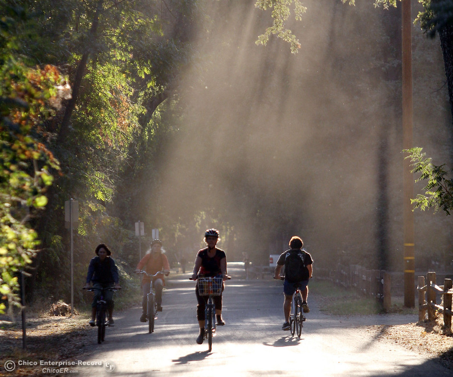 . People ride bicycles as the sun sets east of Caper Acres along South Park Dr. on October 10, 2012 in Chico, Calif. (Jason Halley /Chico Enterprise-Record)