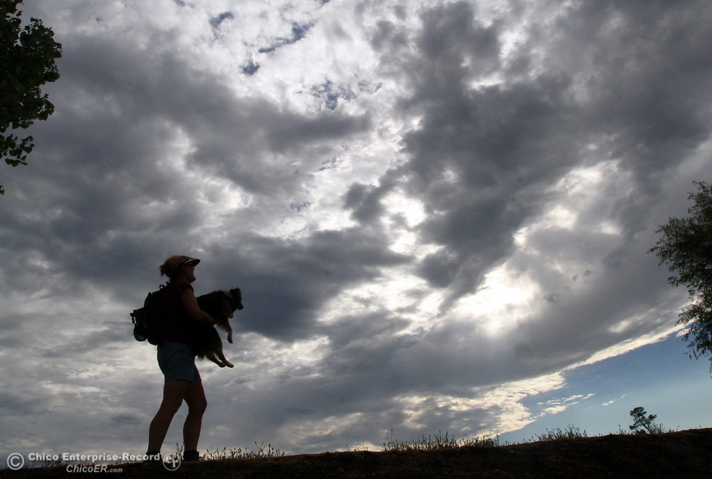 """. Abbie Moriarty, of Chico, takes a moment to view the clouds with her dog \""""Mattie\"""" as they walk along the levee near Horseshoe Lake in upper Bidwell Park on Monday, July 23, 2012. (Ty Barbour/Chico Enterprise-Record)"""