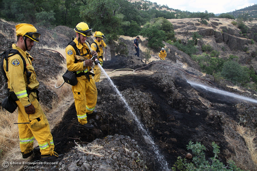 . Chico Fire James Meier (left) and Dominick Peloso (right) hose hot spots at the scene as Chico Fire\'s Engine 15 & Engine 2 were fighting a vegetation fire that is an 1/8th of an acre burning in light fuels next to Bear Hole, in upper Bidwell Park on May 16, 2013 in Chico, Calif.  Several additional fire engines are remaining in a staging area at the pistol range. (Jason Halley/Chico Enterprise-Record)