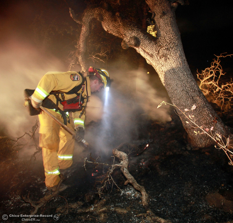 . Cal Fire-Butte County firefighter Matt Watson breaks up hotspots in a fire that broke out late in the night above Salmon Hole in upper Bidwell Park on August 4, 2012 in Chico, Calif. (Jason Halley /Chico Enterprise-Record)