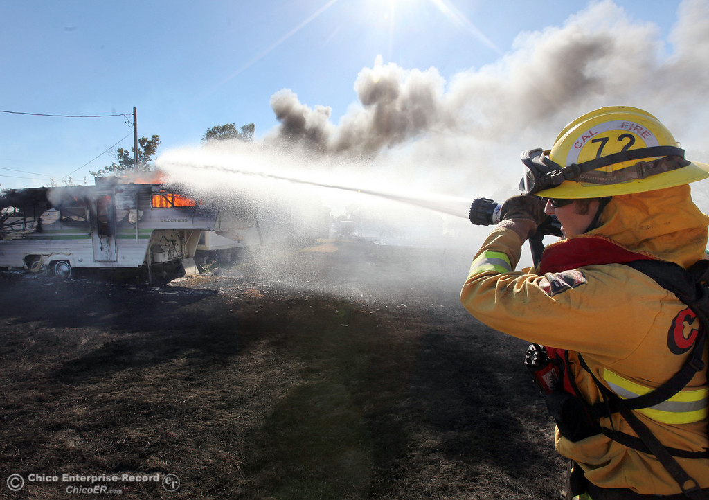 . Cal Fire - Butte County firefighter Clint Siebert hoses a trailer on fire as they battle a vegetation fire off Vineyard Lane Friday, July 12, 2013 in Oroville, Calif.  (Jason Halley/Chico Enterprise-Record)