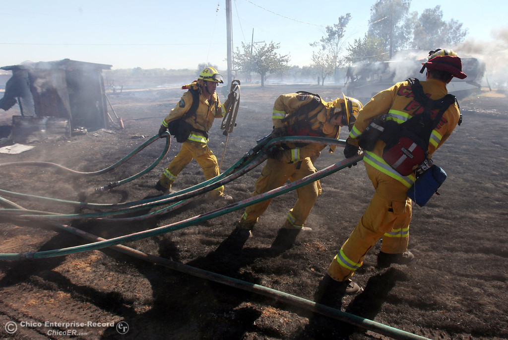 . Cal Fire - Butte County firefighters Ben Holliday, Clint Siebert, and engineer Rob Kenyon (left to right) carry their hose line to battle a fire off Vineyard Lane Friday, July 12, 2013 in Oroville, Calif.  (Jason Halley/Chico Enterprise-Record)