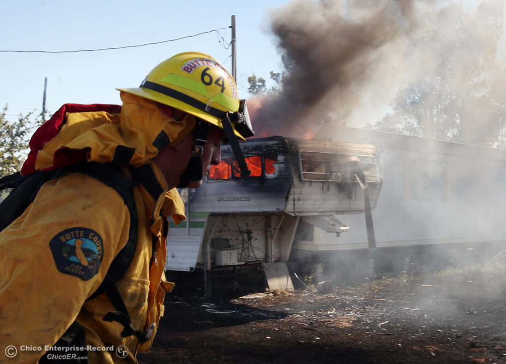. Cal Fire - Butte County firefighter Ben Holliday walks past a trailer on fire as they to battle a fire off Vineyard Lane Friday, July 12, 2013 in Oroville, Calif.  (Jason Halley/Chico Enterprise-Record)