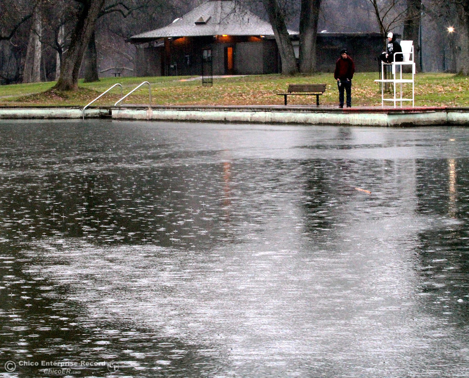 . Ky Abernathy and Amy Roseman stopped to watch the rain droplets hit the water while walking past Sycamore Pool in lower Bidwell Park on January 23, 2013. (Ty Barbour/Chico Enterprise-Record)