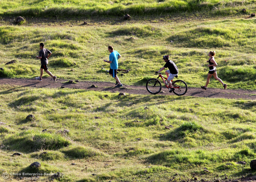. Runners and a bicyclist rides along a trail as people enjoy the warm weather in upper Bidwell Park on March 13, 2013 in Chico, Calif. (Jason Halley/Chico Enterprise-Record)