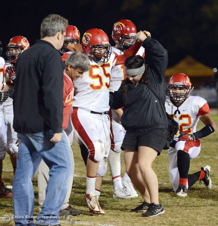 . Chico High\'s #55 Thomas Devlin is carried off the field with an injury against Pleasant Valley High in the first quarter of their Almond Bowl football game at CSUC University Stadium Friday, November 1, 2013 in Chico, Calif.  (Jason Halley/Chico Enterprise-Record)