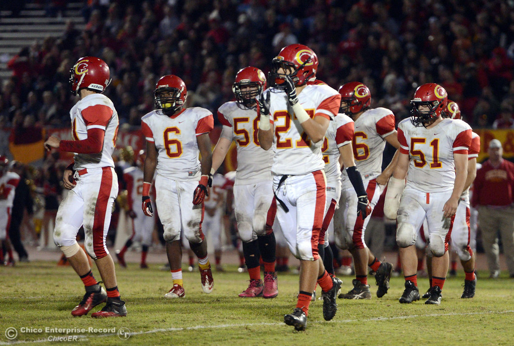 . Chico High\'s #27 Noah Collado (center) and others take the field against Pleasant Valley High in the second quarter of their Almond Bowl football game at CSUC University Stadium Friday, November 1, 2013 in Chico, Calif.  (Jason Halley/Chico Enterprise-Record)