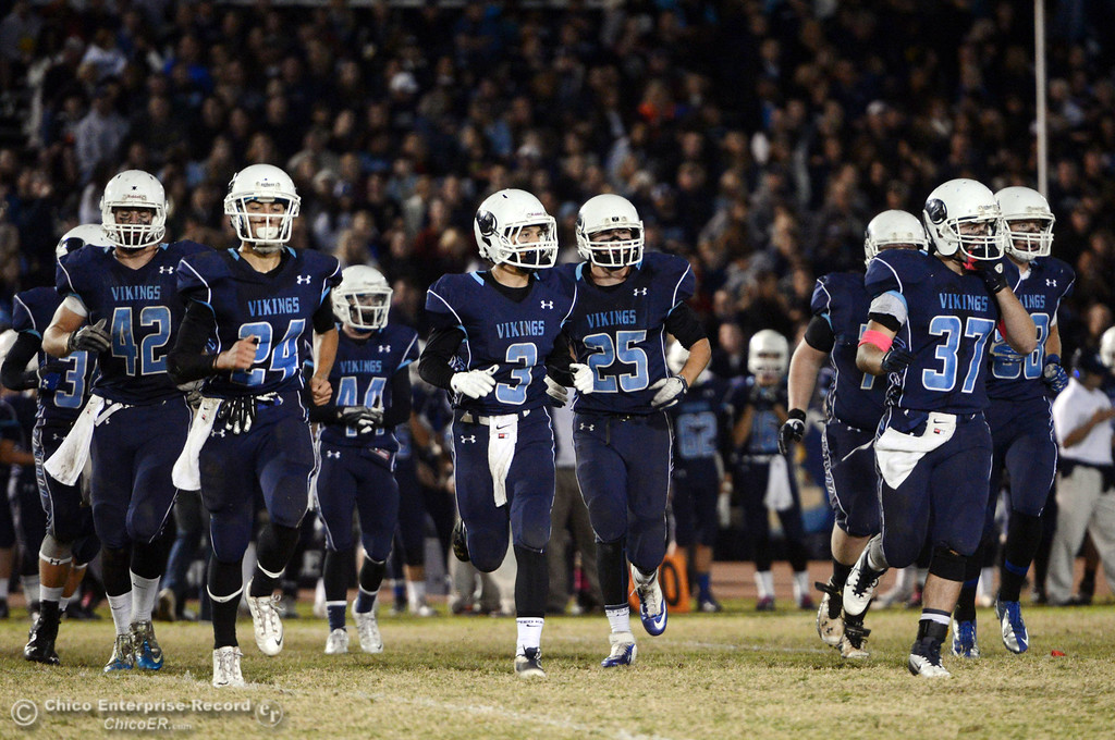 . Pleasant Valley High\'s #42 Chad Olsen, #24 Jack Soza, #3 Brandon Romero, #25 Ryan Steindorf, and #37 Garett Greenwald (left to right) come onto the field against Chico High in the first quarter of their Almond Bowl football game at CSUC University Stadium Friday, November 1, 2013 in Chico, Calif.  (Jason Halley/Chico Enterprise-Record)