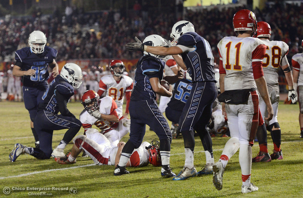 . Pleasant Valley High\'s #42 Chad Olsen (right) celebrates #9 Houston McGowan (center) on scoring a touchdown against Chico High in the third quarter of their Almond Bowl football game at CSUC University Stadium Friday, November 1, 2013 in Chico, Calif.  (Jason Halley/Chico Enterprise-Record)