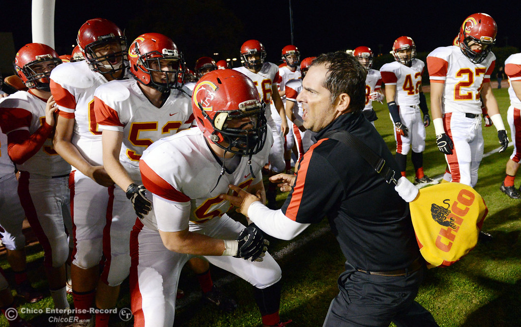 . Chico High\'s coach Jason Alvistur (right) riles up the team against Pleasant Valley High in the first quarter of their Almond Bowl football game at CSUC University Stadium Friday, November 1, 2013 in Chico, Calif.  (Jason Halley/Chico Enterprise-Record)