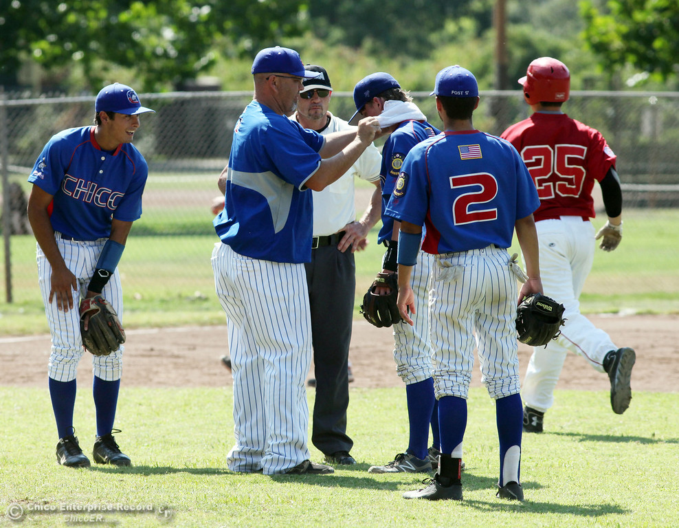 . Chico Nuts\' coach Tom Stevens uses a cold towel to treat #10 Matt Henderson for heat exhaustion against Yolo Post 77 in the top of the second inning during their American Legion baseball game at Doryland field Saturday, July 20, 2013 in Chico, Calif.  (Jason Halley/Chico Enterprise-Record)