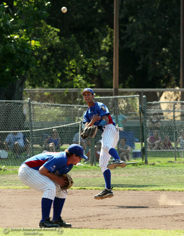 . Chico Nuts\' #33 Andrew Shippelhoute (bottom) ducks under a throw by #12 Michael Sanderson (top) to first base for the force out against Yolo Post 77\'s #18 Hayden Duer (not seen) in the top of the third inning during their American Legion baseball game at Doryland field Saturday, July 20, 2013 in Chico, Calif.  (Jason Halley/Chico Enterprise-Record)