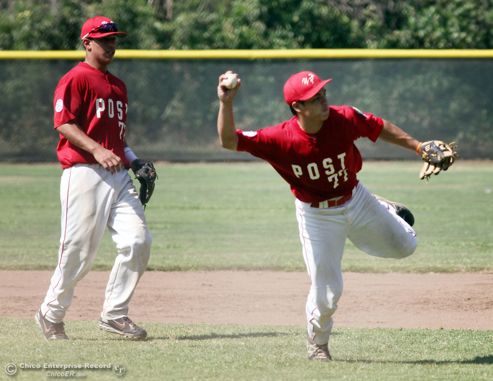 . Yolo Post 77\'s #5 Michael Chavarria (left) watches #4 Joseph Murray (right) attempt to field the ball to first base against Chico Nuts\' #44 Matt Gomes (not seen) in the bottom of the second inning during their American Legion baseball game at Doryland field Saturday, July 20, 2013 in Chico, Calif.  (Jason Halley/Chico Enterprise-Record)