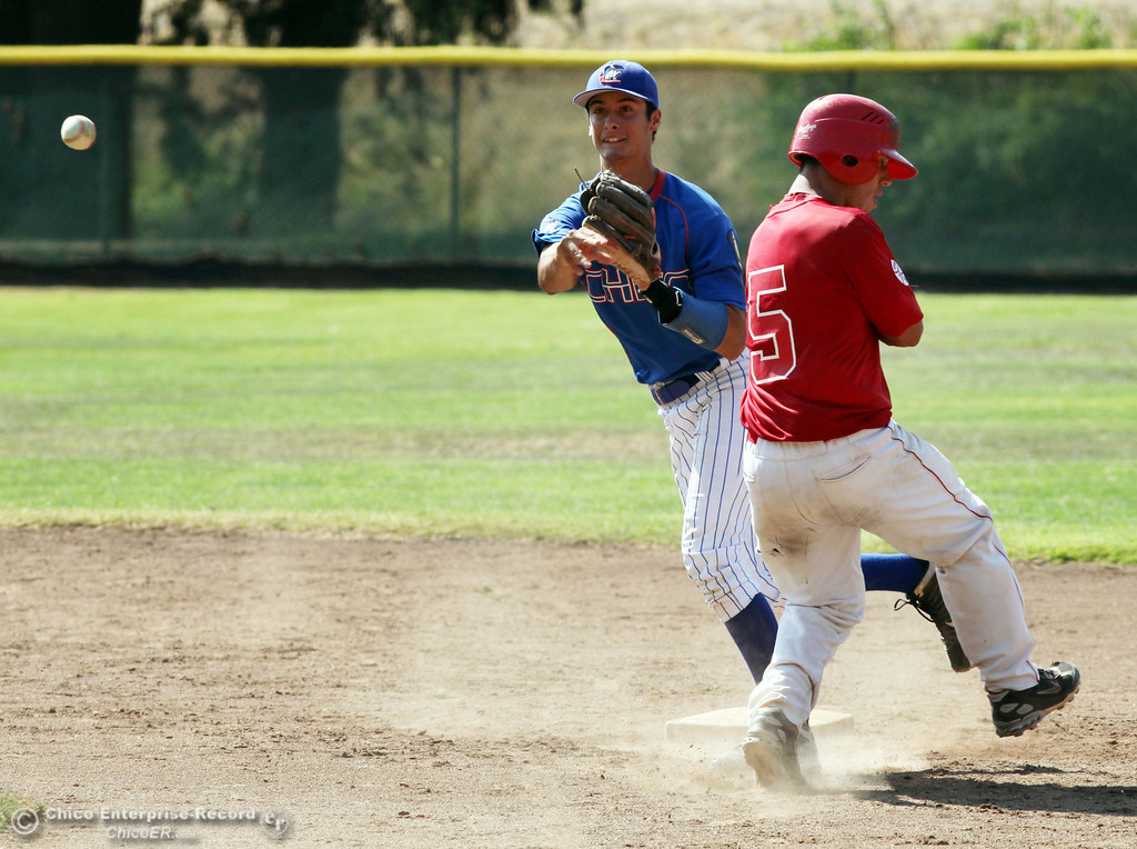 . Chico Nuts\' #12 Michael Sanderson (left) turns the double play from second base against Yolo Post 77\'s #5 Michael Chavarria (right) in the top of the third inning during their American Legion baseball game at Doryland field Saturday, July 20, 2013 in Chico, Calif.  (Jason Halley/Chico Enterprise-Record)