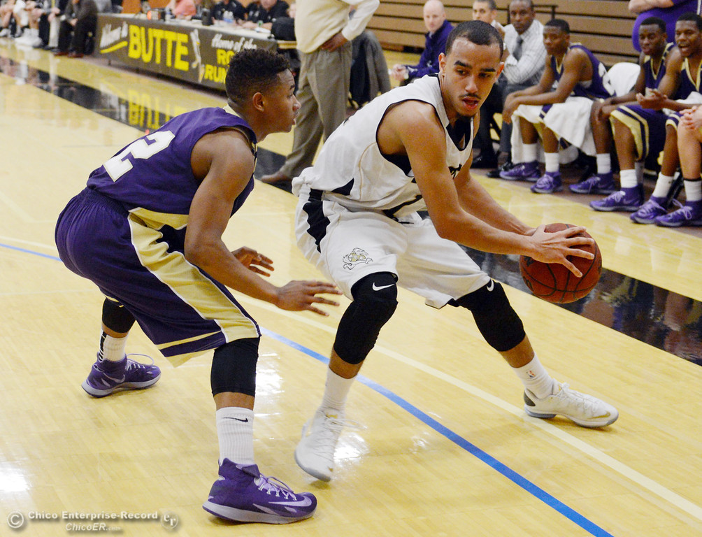 . Butte College\'s #11 Jamaal Davis (right) dribbles against San Jose City College\'s #12 Tyrone Viney (left) in the first half of their men\'s basketball game at Butte\'s Cowan Gym Friday, February 28, 2014 in Oroville, Calif.  (Jason Halley-Chico Enterprise-Record)