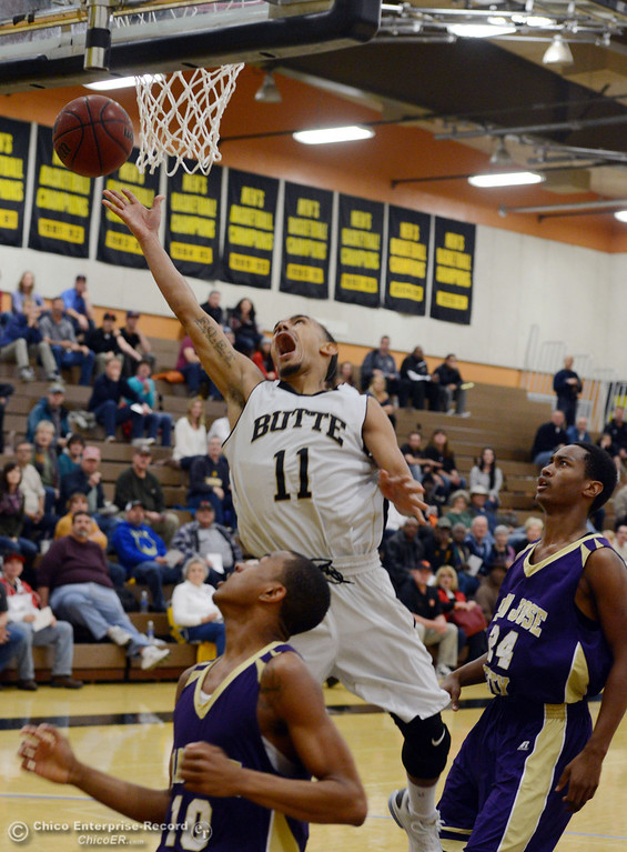 . Butte College\'s #11 Jamaal Davis (center) goes up for a shot against San Jose City College\'s #10 Bobby Gray (left) and #24 Stevinaire Young (right) in the first half of their men\'s basketball game at Butte\'s Cowan Gym Friday, February 28, 2014 in Oroville, Calif.  (Jason Halley-Chico Enterprise-Record)