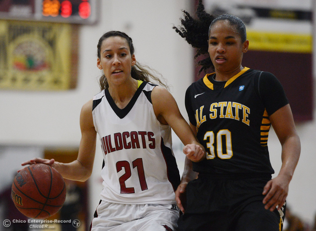 . Chico State\'s #21 Courtney Hamilton (left) dribbles against Cal State L.A.\'s #30 Kaija Powell (right) in the second half of their women\'s basketball game at CSUC Acker Gym Saturday, January 11, 2014 in Chico, Calif.  (Jason Halley/Chico Enterprise-Record)