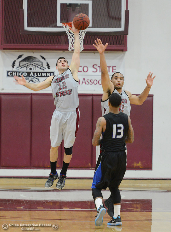 . Chico State\'s #12 Giordano Estrada (left) tips a shot against Cal State San Bernardino\'s #13 Lacy Haddock (right) in the second half of their men\'s basketball game at CSUC Acker Gym Saturday, February 8, 2014 in Chico, Calif.  (Jason Halley/Chico Enterprise-Record)