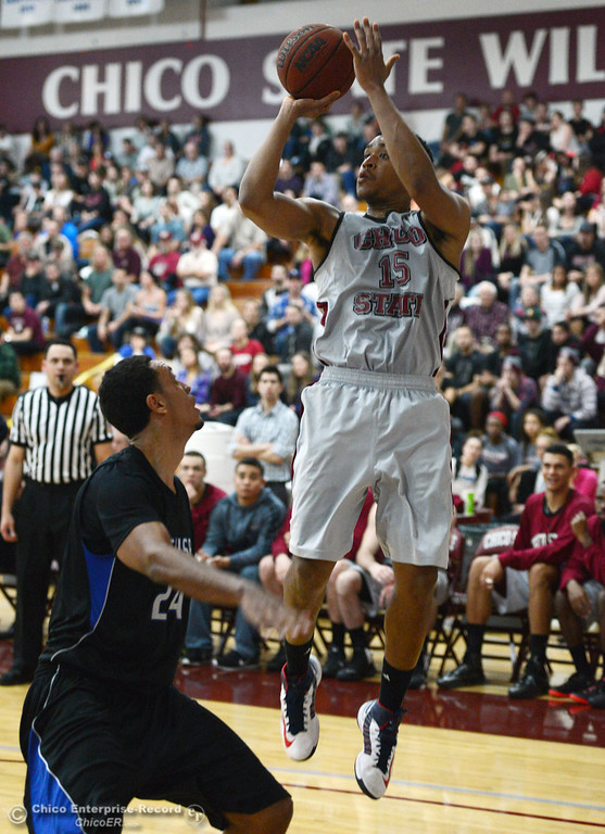 . Chico State\'s #15 Amir Carraway (right) takes a shot against Cal State San Bernardino\'s #24 Jordan Burris (left) in the second half of their men\'s basketball game at CSUC Acker Gym Saturday, February 8, 2014 in Chico, Calif.  (Jason Halley/Chico Enterprise-Record)
