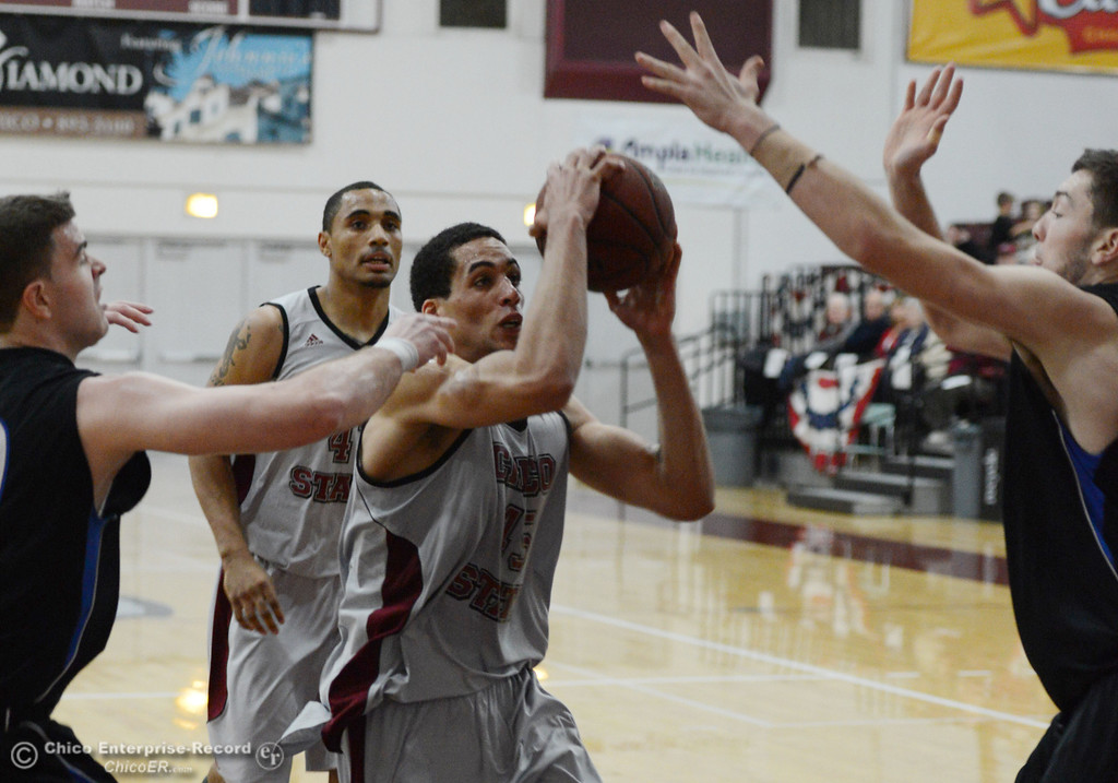 . Chico State\'s #45 Jordan Semple (center) goes up for a shot against Cal State San Bernardino in the first half of their men\'s basketball game at CSUC Acker Gym Saturday, February 8, 2014 in Chico, Calif.  (Jason Halley/Chico Enterprise-Record)