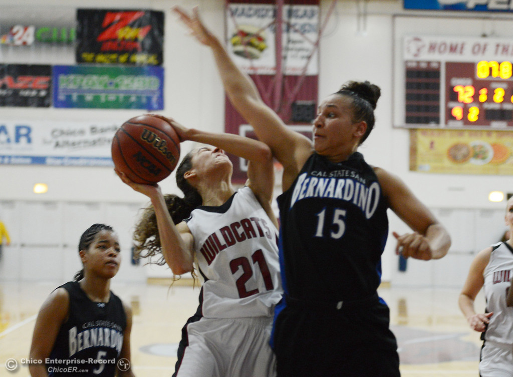 . Chico State\'s #21 Courtney Hamilton (center) dribbles against Cal State San Bernardino\'s #15 Tatiana Dunlap (right) as #5 Tayllor Gipson (left) looks on in the second half of their women\'s basketball game at CSUC Acker Gym Saturday, February 8, 2014 in Chico, Calif.  (Jason Halley/Chico Enterprise-Record)