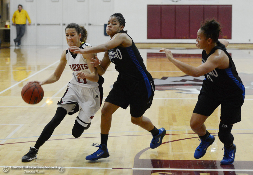 . Chico State\'s #21 Courtney Hamilton (left) dribbles against Cal State San Bernardino\'s #5 Tayllor Gipson (center) and #15 Tatiana Dunlap (right) in the second half of their women\'s basketball game at CSUC Acker Gym Saturday, February 8, 2014 in Chico, Calif.  (Jason Halley/Chico Enterprise-Record)