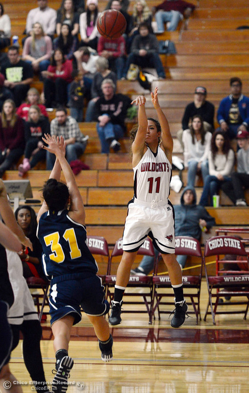 . Chico State\'s #11 Hannah Womack (right) takes a shot against UC San Diego\'s #31 Stephanie Yano (left) in the second half of their women\'s basketball game at CSUC Acker Gym Friday, February 7, 2014 in Chico, Calif.  (Jason Halley/Chico Enterprise-Record)