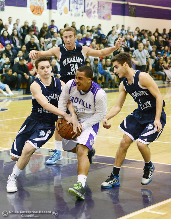 . Oroville High\'s #22 James Jones (center) goes up for a shot against Pleasant Valley High\'s #2 Matt Urrutia, #24 Zack Suttles and #1 Joseph Abdulmasih (left to right) in the fourth quarter of their boys basketball game at OHS Wednesday, February 19, 2014 in Oroville, Calif.  (Jason Halley/Chico Enterprise-Record)