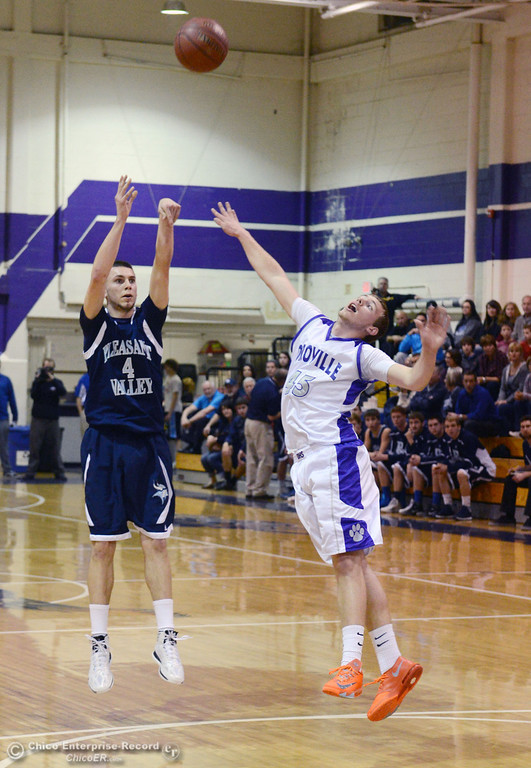 . Pleasant Valley High\'s #4 Jerry Migasi (left) takes a shot against Oroville High\'s #45 Eric Laster (right) in the first quarter of their boys basketball game at OHS Wednesday, February 19, 2014 in Oroville, Calif.  (Jason Halley/Chico Enterprise-Record)