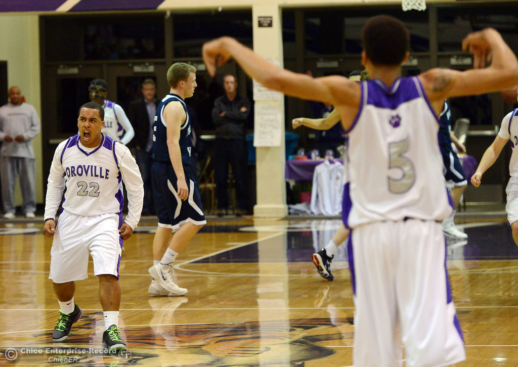 . Oroville High\'s #22 James Jones (left) reacts to scoring against Pleasant Valley High at the buzzer in the first quarter of their boys basketball game at OHS Wednesday, February 19, 2014 in Oroville, Calif.  (Jason Halley/Chico Enterprise-Record)