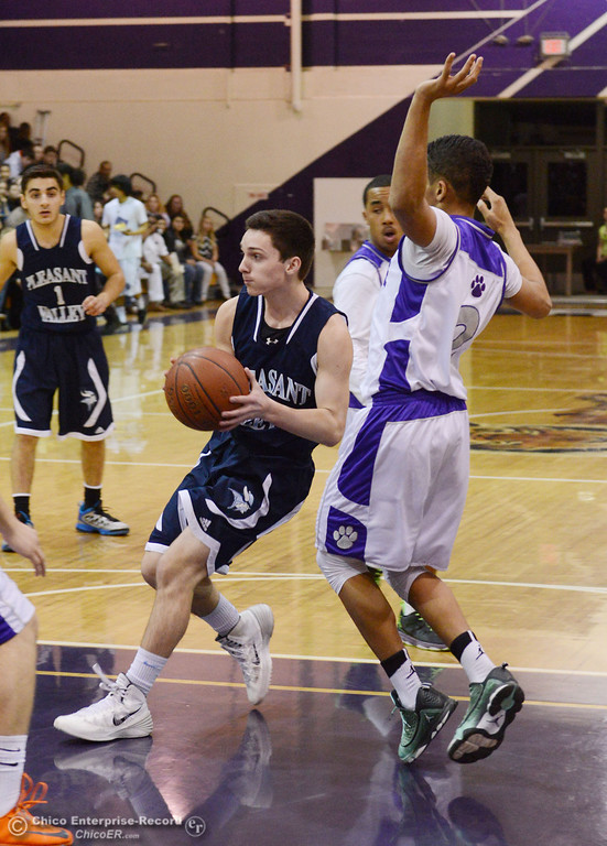 . Pleasant Valley High\'s #2 Matt Urrutia (left) dribbles against Oroville High\'s #2 Marcus Wilhite (right) in the first quarter of their boys basketball game at OHS Wednesday, February 19, 2014 in Oroville, Calif.  (Jason Halley/Chico Enterprise-Record)