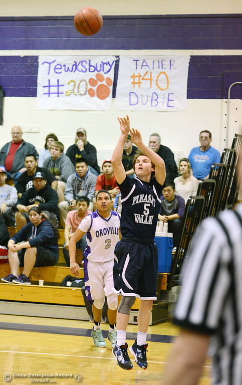 . Pleasant Valley High\'s #5 Tyler Collier (right) takes a shot against Oroville High\'s #2 Marcus Wilhite (left) in the first quarter of their boys basketball game at OHS Wednesday, February 19, 2014 in Oroville, Calif.  (Jason Halley/Chico Enterprise-Record)