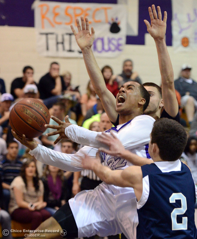 . Oroville High\'s #22 James Jones (center) goes up for a shot against Pleasant Valley High\'s #2 Matt Urrutia (front) and #4 Jerry Migasi (back) in the fourth quarter of their boys basketball game at OHS Wednesday, February 19, 2014 in Oroville, Calif.  (Jason Halley/Chico Enterprise-Record)