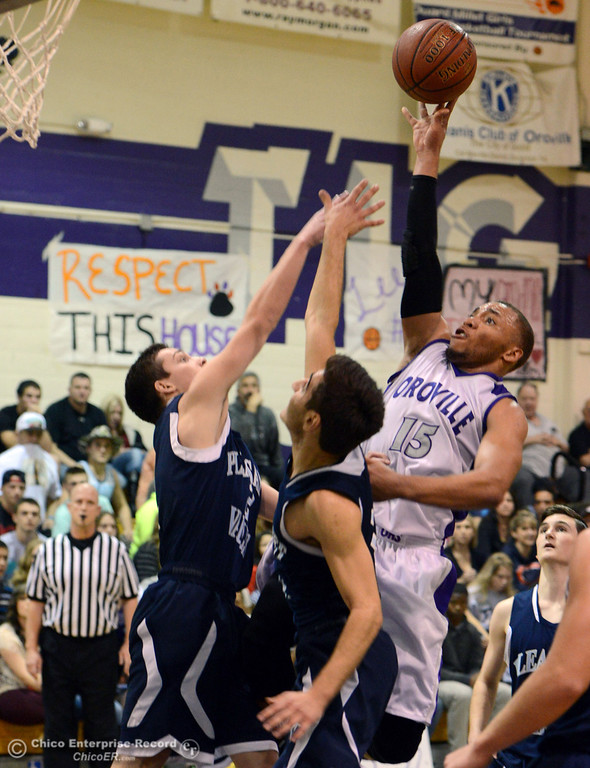 . Oroville High\'s #15 Derrek Gordon (right) goes up for a shot against Pleasant Valley High\'s #1 Joseph Abdulmasih (center) and #2 Matt Urrutia (left) in the fourth quarter of their boys basketball game at OHS Wednesday, February 19, 2014 in Oroville, Calif.  (Jason Halley/Chico Enterprise-Record)