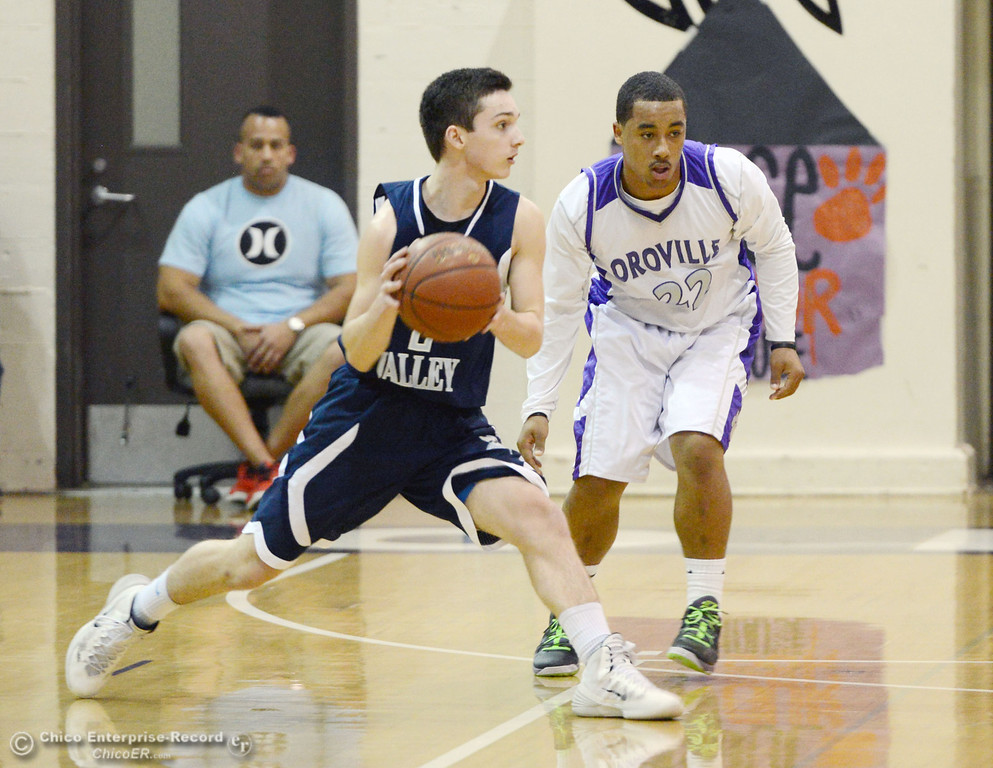 . Pleasant Valley High\'s #2 Matt Urrutia (left) dribbles against Oroville High\'s #22 James Jones (right) in the second quarter of their boys basketball game at OHS Wednesday, February 19, 2014 in Oroville, Calif.  (Jason Halley/Chico Enterprise-Record)