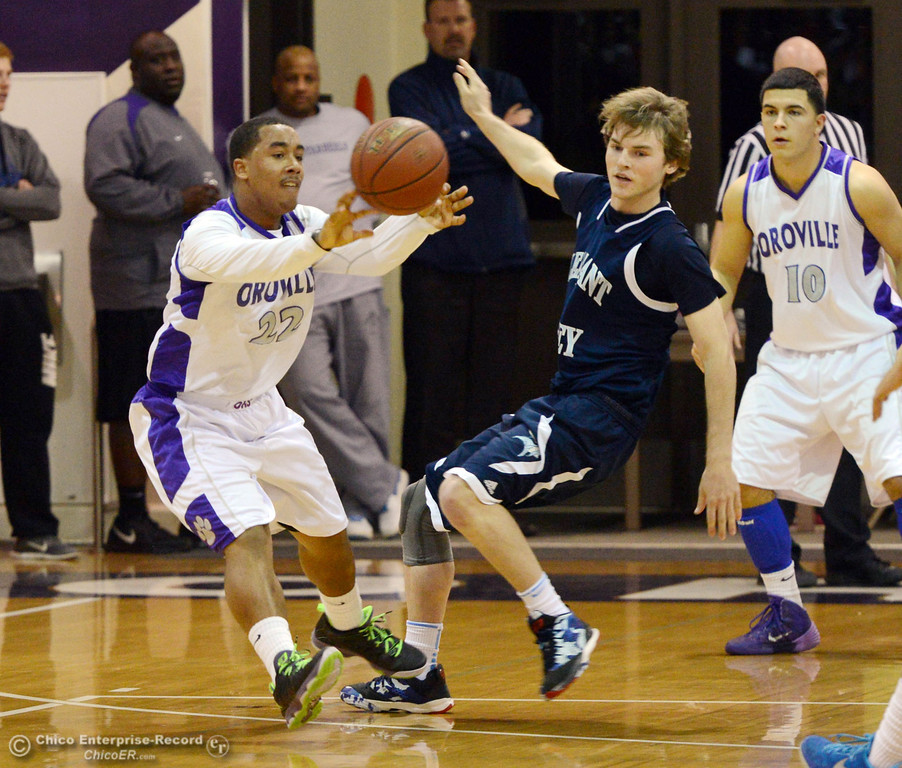 . Oroville High\'s #22 James Jones (left) passes against Pleasant Valley High\'s #5 Tyler Collier (right) in the first quarter of their boys basketball game at OHS Wednesday, February 19, 2014 in Oroville, Calif.  (Jason Halley/Chico Enterprise-Record)