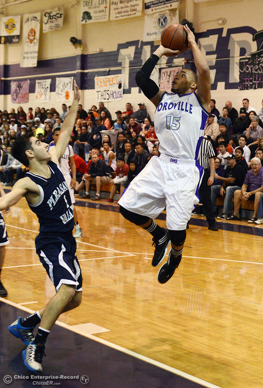 . Oroville High\'s #15 Derrek Gordon (right) takes a shot against Pleasant Valley High\'s #1 Joseph Abdulmasih (left) in the second quarter of their boys basketball game at OHS Wednesday, February 19, 2014 in Oroville, Calif.  (Jason Halley/Chico Enterprise-Record)