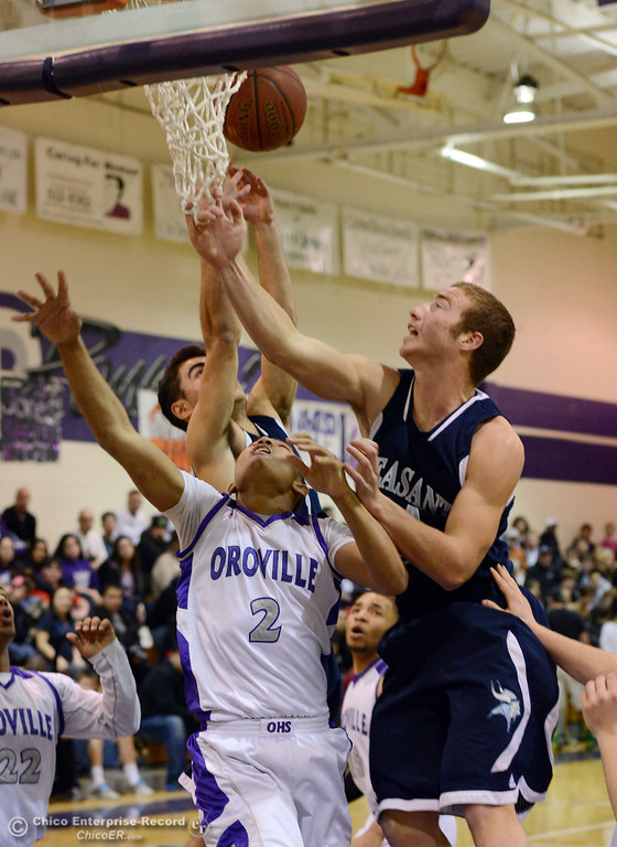 . Pleasant Valley High\'s #1 Joseph Abdulmasih (back) and #24 Zack Suttles (right) rebound against Oroville High\'s #2 Marcus Wilhite (center) in the first quarter of their boys basketball game at OHS Wednesday, February 19, 2014 in Oroville, Calif.  (Jason Halley/Chico Enterprise-Record)