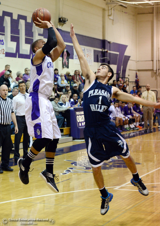 . Oroville High\'s #15 Derrek Gordon (left) takes a shot against Pleasant Valley High\'s #1 Joseph Abdulmasih (right) in the second quarter of their boys basketball game at OHS Wednesday, February 19, 2014 in Oroville, Calif.  (Jason Halley/Chico Enterprise-Record)