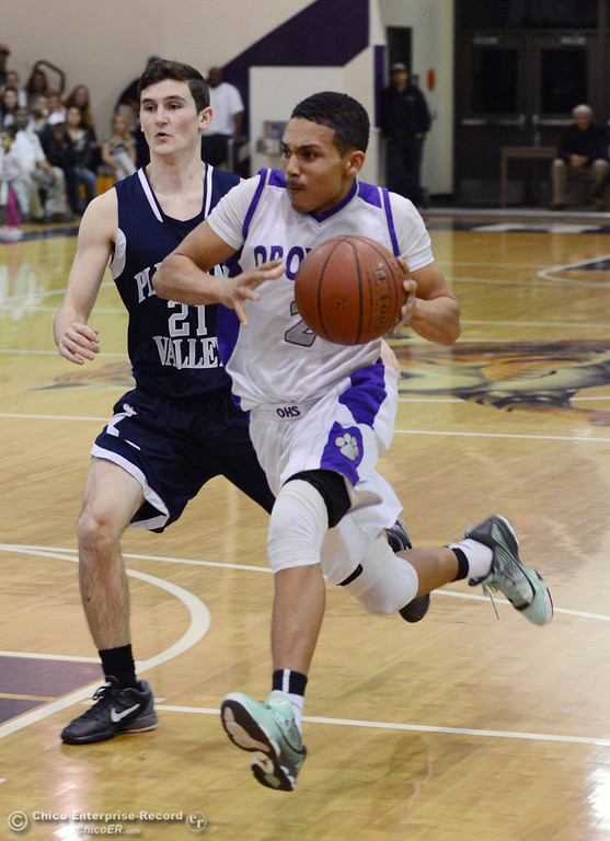. Oroville High\'s #2 Marcus Wilhite (right) dribbles against Pleasant Valley High\'s #21 Drew Minkler (left) in the fourth quarter of their boys basketball game at OHS Wednesday, February 19, 2014 in Oroville, Calif.  (Jason Halley/Chico Enterprise-Record)