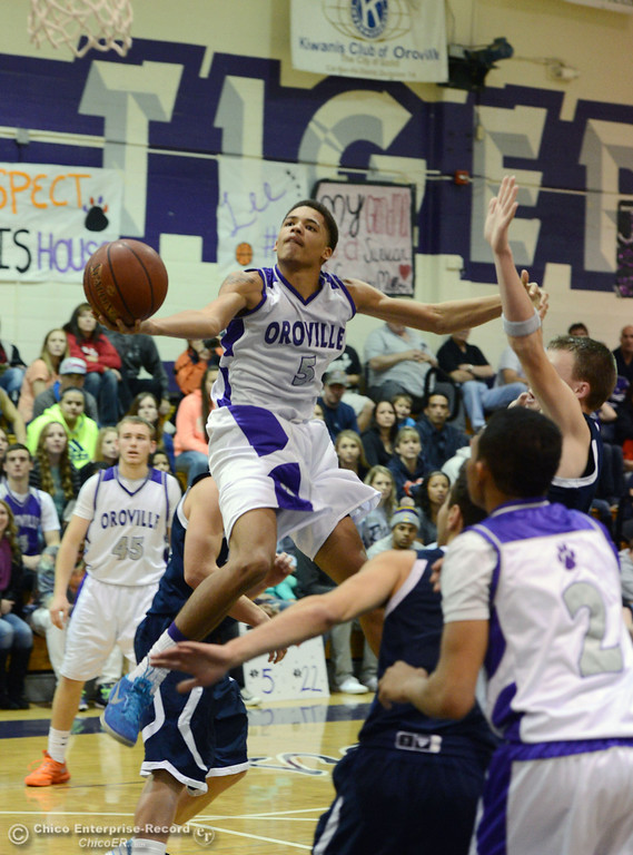 . Oroville High\'s #5 Kahliel Wyatt (center) goes up for a shot against Pleasant Valley High in the fourth quarter of their boys basketball game at OHS Wednesday, February 19, 2014 in Oroville, Calif.  (Jason Halley/Chico Enterprise-Record)
