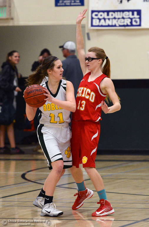 . Chico High\'s #13 Sharlotte Sheffield (right) defends against Paradise High\'s #11 Cassidy Burnett (left) in the first quarter of their girls basketball game at PHS Tuesday, February 18, 2014 in Paradise, Calif.  (Jason Halley/Chico Enterprise-Record)