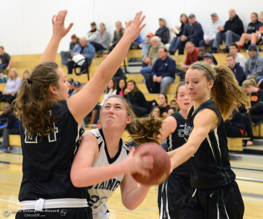 . Pleasant Valley High\'s #25 Courtney Holloway (center) goes up for a shot against Colfax High\'s #24 Makenna Glisson (left) and #3 Kyra Heimann (right) in the second quarter of their girls basketball game at PV\'s Varley Gym Saturday, December 7, 2013 in Chico, Calif. (Jason Halley/Chico Enterprise-Record)