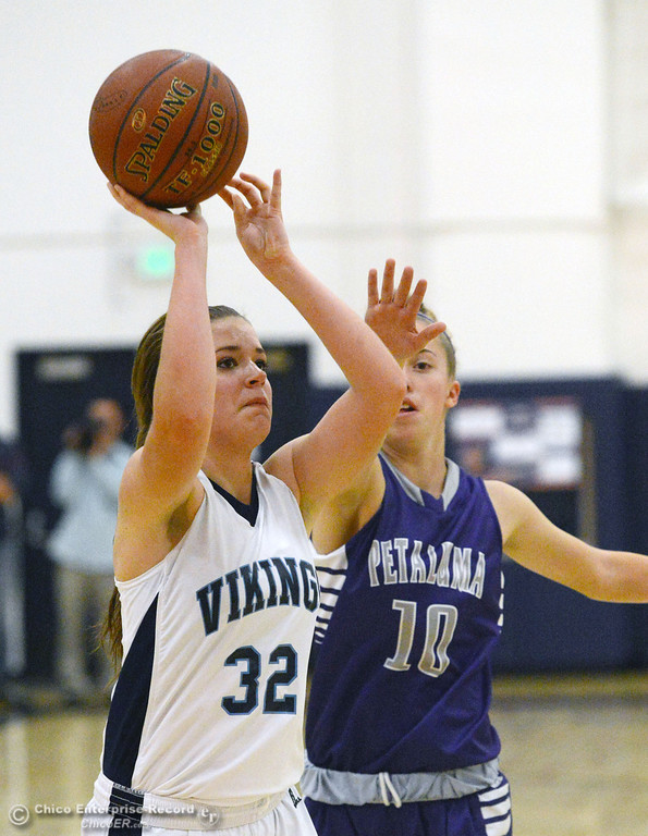 . Pleasant Valley High\'s #32 Natalie Makel (left) takes a shot against Petaluma High\'s #10 Emily Corda (right) in the first quarter of their girls basketball game at PVHS Varley Gym Friday, December 6, 2013 in Chico, Calif. (Jason Halley/Chico Enterprise-Record)