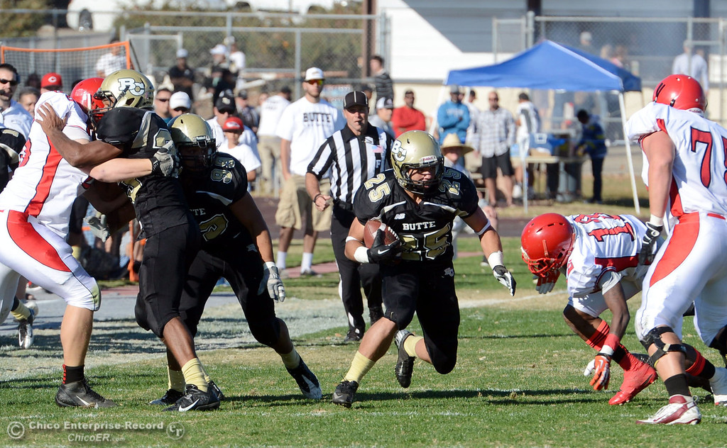. Butte College\'s #25 De\'Aundray Gooden (center) picks up the ball against City College of San Francisco in the second quarter of their football game at Butte\'s Cowan Stadium Saturday, November 16, 2013 in Butte Valley, Calif.  (Jason Halley/Chico Enterprise-Record)