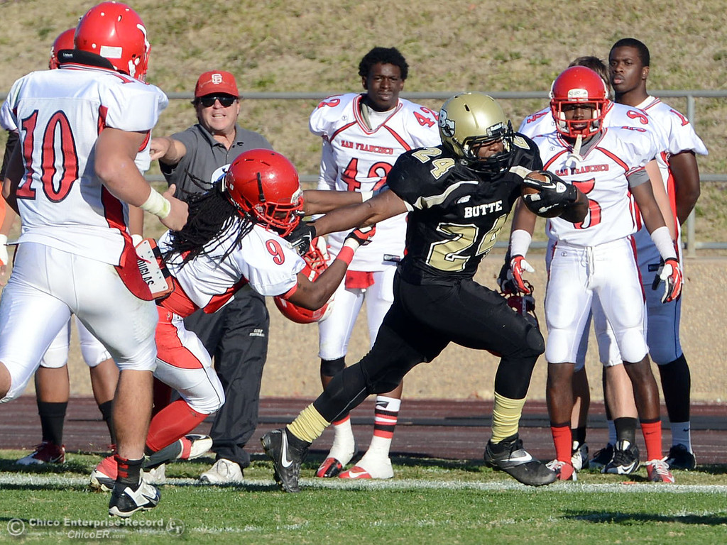 . Butte College\'s #24 Kendall Williams (right) is tackled by City College of San Francisco\'s #9 Uriah Harris (left) in the third quarter of their football game at Butte\'s Cowan Stadium Saturday, November 16, 2013 in Butte Valley, Calif.  (Jason Halley/Chico Enterprise-Record)