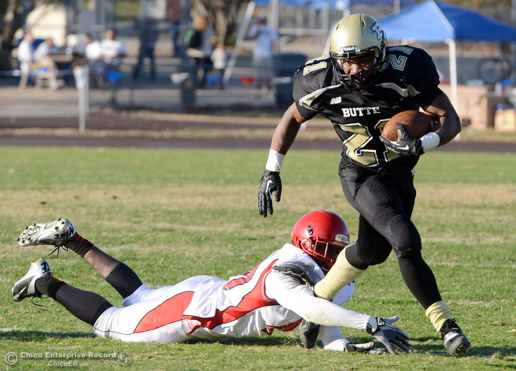 . Butte College\'s #21 Marvel Harris (right) breaks the tackle against City College of San Francisco\'s #40 Brendan Royal (left) in the third quarter of their football game at Butte\'s Cowan Stadium Saturday, November 16, 2013 in Butte Valley, Calif.  (Jason Halley/Chico Enterprise-Record)